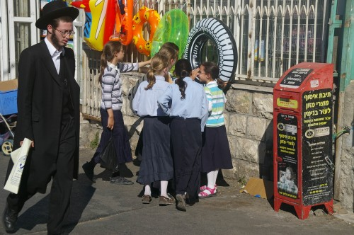 Imagen típica de una calle de Jerusalem. Un judío ortodoxo se pasea por una acera en la que juegan varias niñas con su singular atuendo